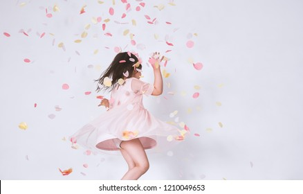 Cheerful cute little girl wearing pink dress in tulle with princess crown dancing on confetti surprise isolated on white studio wall. Playful toddler girl celebrating her birthday party having fun