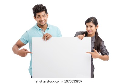 Cheerful cute young couples holding and pointing white board on white.