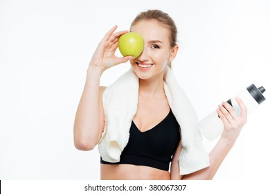 Cheerful cute young sportswoman covered eye with apple over white background