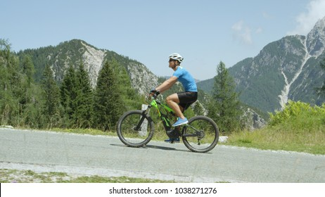 Cheerful cyclist riding his innovative electric bicycle up an asphalt hill in the sunny mountains. Happy Caucasian male rides cool e-bike and looks at beautiful green and sunny nature surrounding him