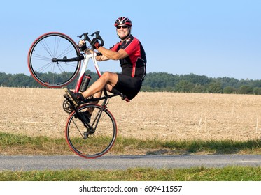 Cheerful cyclist riding on the rear wheel. Biker balancing while driving on a road bike. Risky ride on one wheel.