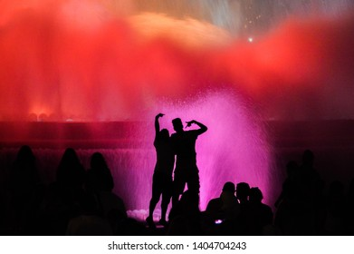 Cheerful dark black silhouettes of people a couple of girls and a guy on the background of colorful bright magical fountain of Barcelona red, pink and orange