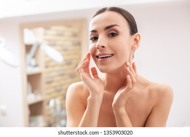 Cheerful dark haired lady standing with bare shoulders and smiling while putting her hands to the face