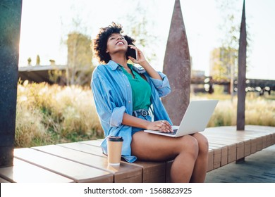 Cheerful dark skinned hipster girl blogger having fun while typing on laptop computer and making telephone call ,happy woman freelancer satisfied with 4G connection for work remotely on street