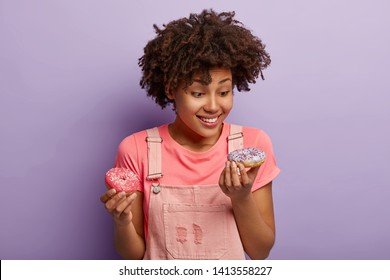 Cheerful dark skinned woman eats delicious doughnut, looks happily at tasty dessert, wears casual pink t shirt and overalls, isolated over purple background. Female enjoys sprinkled sweet donut