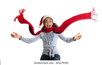 cheerful dark-skinned girl in a red scarf and hat of Santa Claus. Winter portrait of joyful adolescent girls