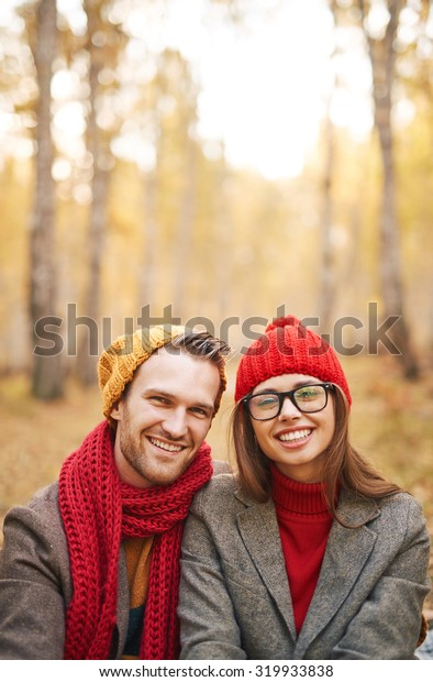 Cheerful dates in warm stylish clothes looking at camera with smiles
