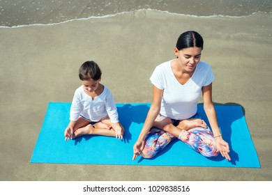 cheerful daughter and beautiful mother practice yoga and meditate together on the beach