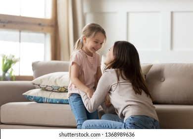 Cheerful daughter looking at overjoyed mother laughing having fun in living room at home, older younger sister enjoy time together spend funny activity on weekend, love and care tender moment concept