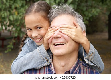 Cheerful daughter surprising her father