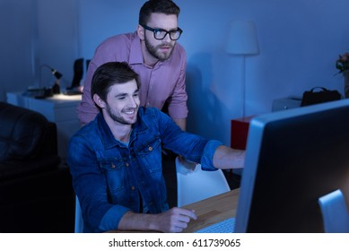 Cheerful delighted programmer smiling