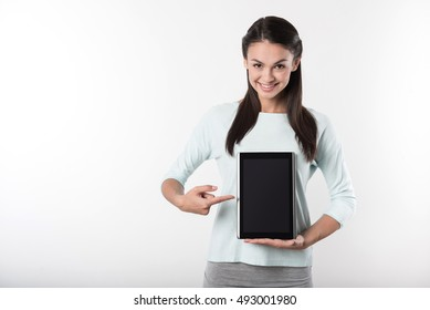Cheerful delighted woman holding tablet