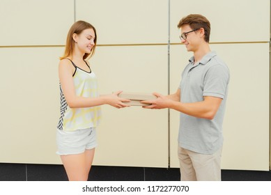Cheerful delivery man in eyeglasses giving two boxes with pizza to attractive happy girl, outdoors. Delivery concept.