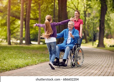 cheerful disabled grandfather in wheelchair welcoming his happy granddaughter