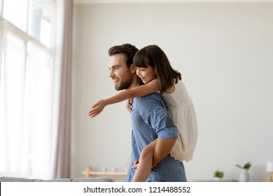 Cheerful diverse active family having fun playing together at home. Happy little adorable sweet daughter piggybacks her young handsome father man carrying loving child on his back looking at window