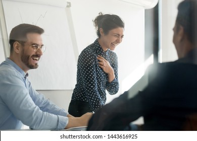 Cheerful diverse business team workers group laughing having fun at corporate training, happy young indian female coach having fun with male colleagues talk joke in conference room at office briefing