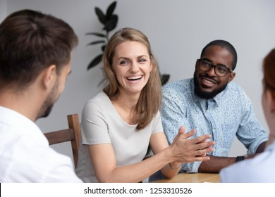 Cheerful diverse millennial colleagues sitting at desk before business lecture chatting having good relations in collective. Experienced young coach talking with company members joking during seminar