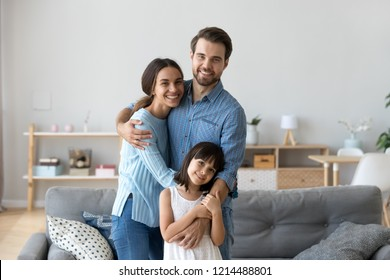 Cheerful diverse multi-ethnic family married couple wife husband little daughter embracing standing together in living room smiling looking at camera at new modern home feels happy and satisfied