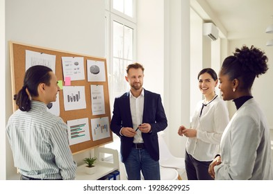 Cheerful diverse office workers discuss financial risks and analyze charts and diagrams together. Positive colleagues discuss a new business project. Concept of planning, brainstorming and teamwork.