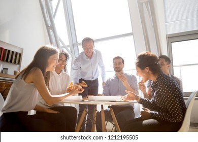 Cheerful diverse team people workers students laughing at funny joke while eating pizza together, friendly multi-ethnic colleagues group talking enjoying having fun and corporate lunch in office room - Shutterstock ID 1212195505