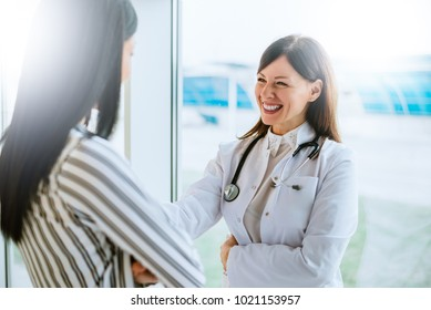 Cheerful doctor talking with her patient near window.