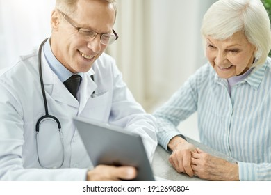 Cheerful doctor using tablet computer while talking with old lady