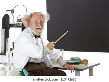 Cheerful eccentric senior scientist in his lab points to blackboard and explains his ideas. High key, horizontal, copy space.