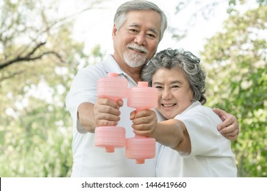 Cheerful elderly Asian man and senior Asian woman with dumbbell for workout in park, They smiling with good healthy together , senior Asian couple concept