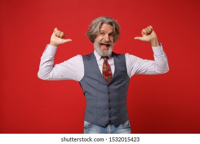 Cheerful elderly gray-haired mustache bearded man in classic shirt vest and colorful tie isolated on red background in studio. People lifestyle concept. Mock up copy space. Pointing thumbs on himself
