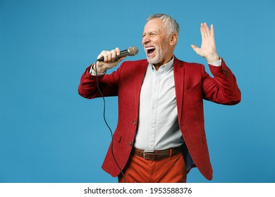 Cheerful elderly gray-haired mustache bearded business man wearing red jacket suit standing sing song in microphone spreading hands looking aside isolated on blue color background studio portrait