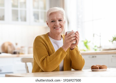 Cheerful elderly lady drinking coffee with croissant, sitting in kitchen at home, having snack, copy space. Attractive senior woman enjoying cup of herbal tea with home baked pastry