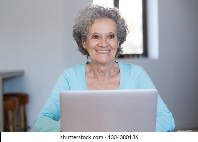 Cheerful elderly lady successfully mastering computer skills. Senior woman in casual working on laptop at home. Computer skills concept