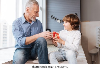 Cheerful elderly man giving a present to his grandson
