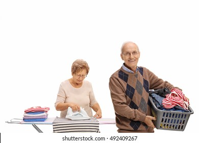 Cheerful elderly man holding a laundry basket and a mature woman ironing isolated on white background