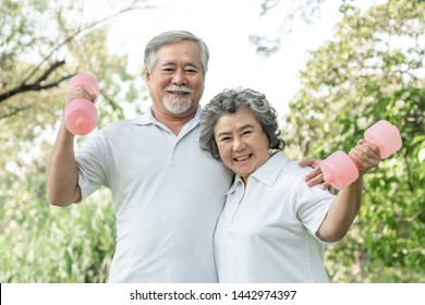 Cheerful elderly man and senior woman with dumbbell for workout in park, They smiling with good healthy together