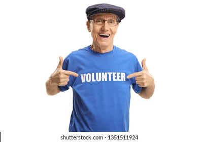Cheerful elderly man wearing a volunteer signed t-shirt and pointing at it isolated on white background