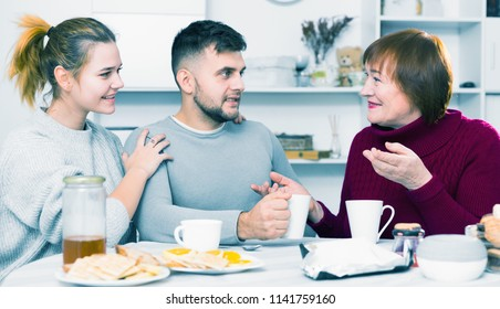 Cheerful elderly mother having good time with adult children drinking tea in kitchen