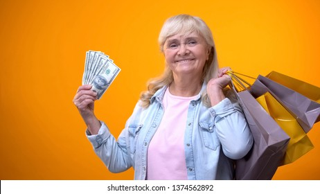 Cheerful elderly woman holding shopping bags and dollar cash, consumerism