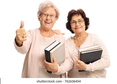 Cheerful elderly women with books making a thumb up gesture isolated on white background