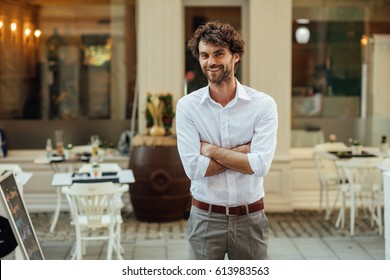 cheerful elegant man, standing outside in the street in front of his restaurant