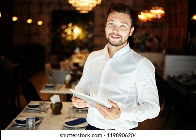 Cheerful elegant man in white shirt holding tablet and smiling at camera standing in modern restaurant