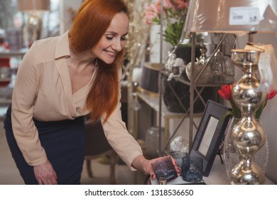 Cheerful elegant mature woman smiling joyfully, shopping at homeware store, examining candle holder, copy space. Attractive female customer buying home goods. Consumerism, home fashion concept