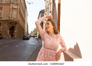 Cheerful elegant model wearing pink lace dress, posing at the ancient street of Lvov