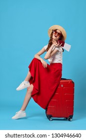 Cheerful elegant woman in a red skirt with a hat and glasses is sitting on a suitcase on a blue background