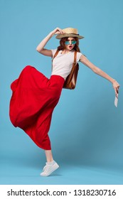 A cheerful elegant woman in a red skirt will be holding a passport in her hands with tickets for a plane on a blue background