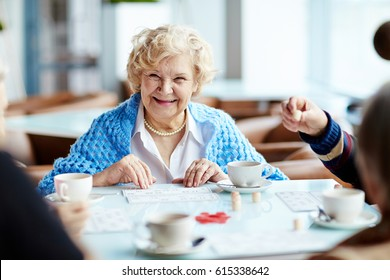 Cheerful elegant-looking elderly woman gathered with her friends in lovely coffeehouse and playing lotto enthusiastically