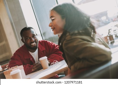 Cheerful emotional bearded man sitting next to the window in the cafe and smiling while looking at his beautiful girlfriend