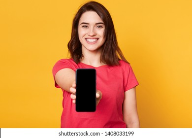Cheerful energetic black haired female reaching out arm, holding smartphone in one hand, smiling sincerely, looking directly at camera, being in high spirits, wearing casual bright red t shirt.