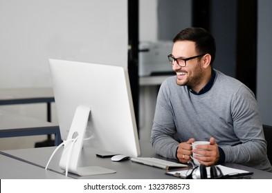 Cheerful entrepreneur at this office looking at monitor with a smile and holding coffee cup