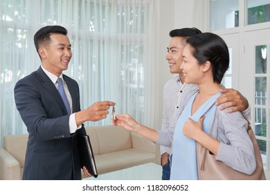 Cheerful estate broker giving keys to happy young Asian couple